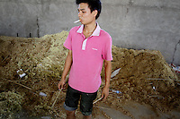 A factory worker smokes near a pile of sawdust, inside a factory that produces furniture and chopsticks made of bamboo. Sichuan Province.