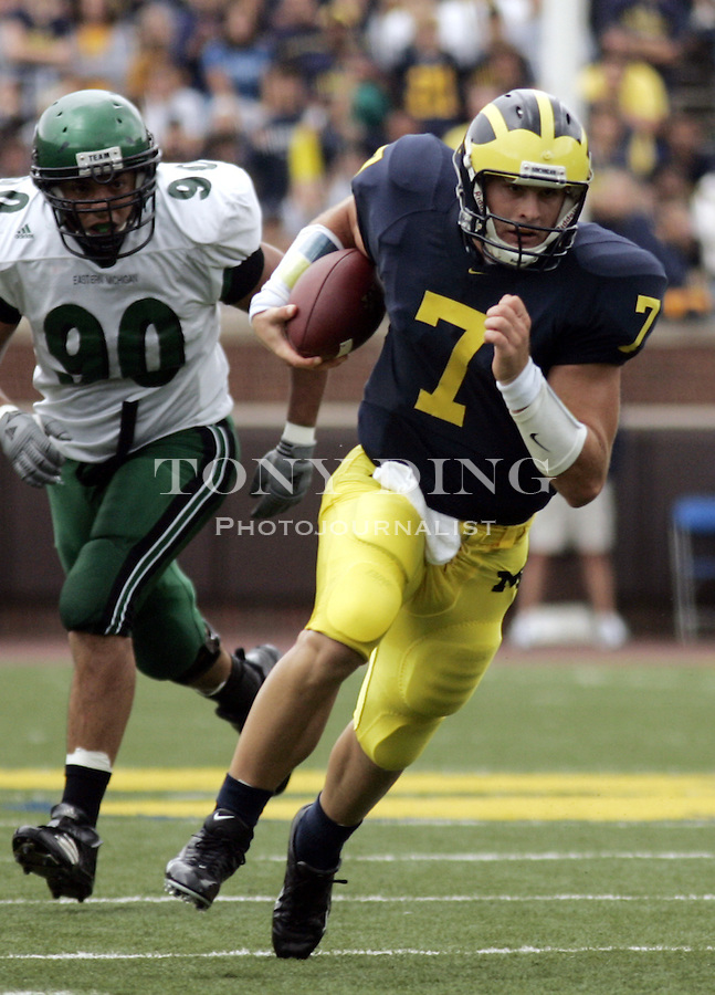 Michigan quarterback Chad Henne (7) scrambles while being chased by Eastern Michigan defensive end Jean-Olivier Gagnon-Gordillo (90) during the second quarter in Ann Arbor, Mich., Saturday, Sept. 17, 2005. Max Martin ran for two touchdowns, then Henne threw two TD passes to Jason Avant as No. 14 Michigan tied a school record with 28 points in the first quarter and went on to roll over Eastern Michigan 55-0.  (AP Photo/Tony Ding)