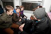Der Schulweg in einem Zug zum Stadtrand. Nichtstaatliche Schule in Belarus in der Nähe von Minsk, deren Schüler und Lehrer lange Wege und Überwachung in Kauf nehmen. / Pupils on their way to school in a train. Privat school in Belarus near Minsk.