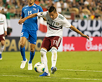 CHARLOTTE, NC - JUNE 23: Roberto Alvarado #11 shoots on goal during a game between Mexico and Martinique at Bank of America Stadium on June 23, 2019 in Charlotte, North Carolina.