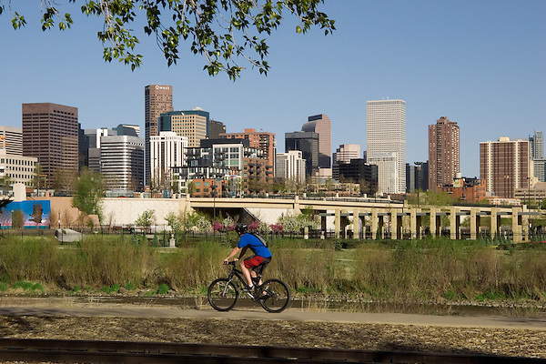 Young Caucasian male biking in Confluence Park, with downtown Denver behind, Denver, Colorado, USA .  John offers private photo tours in Denver, Boulder and throughout Colorado. Year-round.