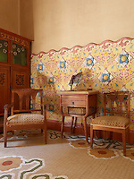 Two upholstered chairs in a tiled bedroom, their chequered pattern echoing the geometric shapes on the tiled floor