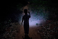 A child lights his way using a torch in the village of 2500 people that is off the electricity grid.