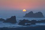 Sun setting into offshore fog bank at Harris Beach State Park, Oregon coast..#06061005