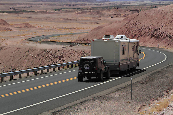 Recreational vehicle pulling 4WD Jeep on Highway 160 in the Painted Desert on the Navajo Indian Reservation, near Tuba City in northern Arizona, USA . John offers private photo tours in Grand Canyon National Park and throughout Arizona, Utah and Colorado. Year-round.