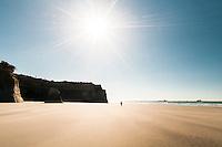 Woman walking on Carters Beach near Westport,  Buller Region, Central West Coast, New Zealand