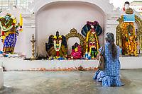 Woman Praying to Hindu Deities, Hindu Sri Maha Muneswarar Temple, Kuala Lumpur, Malaysia.