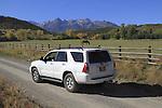 White SUV on dirt road in the Sneffels Range near Telluride, Colorado, USA.