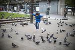 """© Joel Goodman - 07973 332324 . 06/04/2017 . Manchester , UK . A boy runs through a flock of pigeons in front of architect Tadao Ando's concrete wall - known locally as """" The Berlin Wall """" -  in Piccadilly Gardens . An epidemic of abuse of the drug spice by some of Manchester's homeless population , in plain sight , is causing users to experience psychosis and a zombie-like state and is daily being witnessed in the Piccadilly Gardens area of Manchester , drawing large resource from paramedic services in the city centre . Photo credit : Joel Goodman"""
