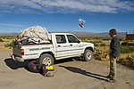 Andean Mountain Cat (Leopardus jacobita) biologists, Juan Reppucci and Mauro Lucherini, checking car before heading into the mountains, Laguna de los Pozuelos Natural Monument, Andes, northwestern Argentina