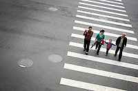 CHINA. Beijing. A family cross the road at a city intersection. Manholes dot the roads, linking to sewer systems and maintenance routes. 2009