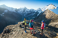 Runners stand on the summit of the Pigne de la Lé after hiking up it for sunrise, during the Via Valais, a multi-day trail running tour connecting Verbier with Zermatt, Switzerland.
