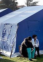 Un uomo e una donna nella tendopoli allestita per accogliere gli sfollati, in piazza d'Armi, all'Aquila, in Abruzzo, 8  aprile 2009, dopo il terremoto che ha colpito la regione..A man reacts as he sits past a woman in a tent-camp set up by the civil protection agency, in L'Aquila, central Italy, 8 april 2009, to put up survivors of the earthquake that hit the region Abruzzo..UPDATE IMAGES PRESS/Riccardo De Luca