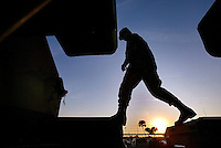 Corporal James Harris, of Winter Park, walks across the front of a line of Avenger anti-aircraft systems as National Guard reservists work late into the evening Thursday March 13, 2003 preparing for their deployment for the possible war in Iraq at the National Guard Armory in Daytona Beach.(Kelly Jordan)..**FOR ONLINE GALLERY**