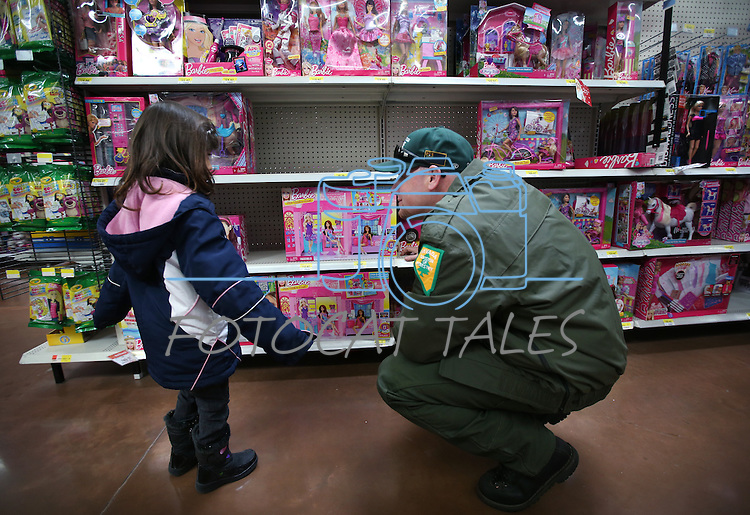 Paul Carmichael, with NDF, helps one of nearly 170 elementary students shop as part of the Holiday with a Hero program at Walmart in Carson City, Nev., on Tuesday, Dec. 17, 2013. The community event partners military, firefighters, law enforcement and medical personnel with local Students in Transition to provide them with Christmas presents.<br /> Photo by Cathleen Allison