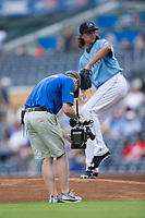 A video camera operator gets a close up of Durham Bulls starting pitcher Brent Honeywell (21) as he warms up prior to the start of the game against the Buffalo Bisons at Durham Bulls Athletic Park on April 30, 2017 in Durham, North Carolina.  The Bisons defeated the Bulls 6-1.  (Brian Westerholt/Four Seam Images)