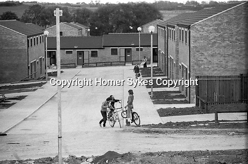 1970s England new town under development, houses built, but not all works yet finished, gardens not planted, but new residents have  and are moving in.  Children playing in the empty street on their bikes 1977 Milton Keynes Buckinghamshire.