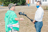 An television reporter interviews a demonstrator with a bullhorn labeled Trump 2020 as the alt-right organization Super Happy Fun America demonstrates against facemasks, vaccines, and pandemic closures, and in support of the reelection of President Donald J. Trump near the residence of Massachusetts governor Charlie Baker in Swampscott, Massachusetts, on Sat., Sept. 26, 2020. Super Happy Fun America is most well known for organizing the Straight Pride Parade in Boston on August 31, 2019.