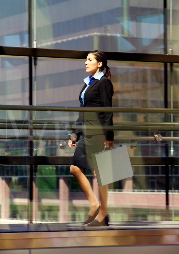 Successful business woman in business suit walking with briefcase.