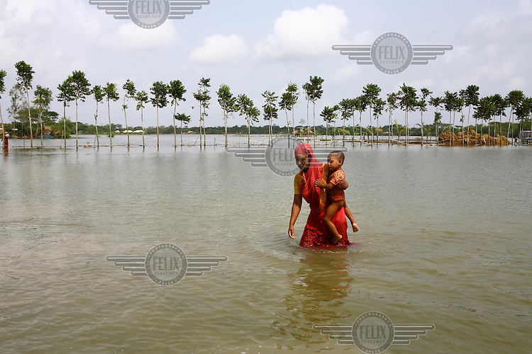 A mother carries her child through the floodwaters. Thousands of people were displaced in Shyamnagar Upazila, Satkhira district after Cyclone Aila struck Bangladesh on 25/05/2009, triggering tidal surges and floods..