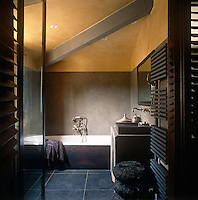 A modern bathroom with a yellow painted ceiling and a grey tiled floor. A washbasin is set on a stone plinth, which stands next to a bath.