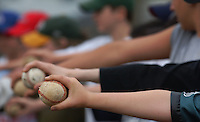 Young boys practicing for pitchers hold the ball for inspection during summer baseball league