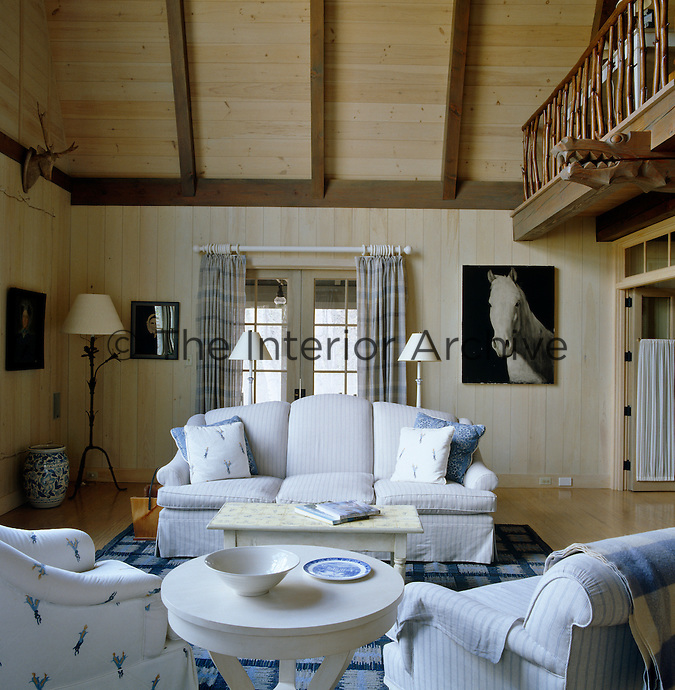 This Swedish-style pine-clad living room has a gallery and is furnished simply in blue and white