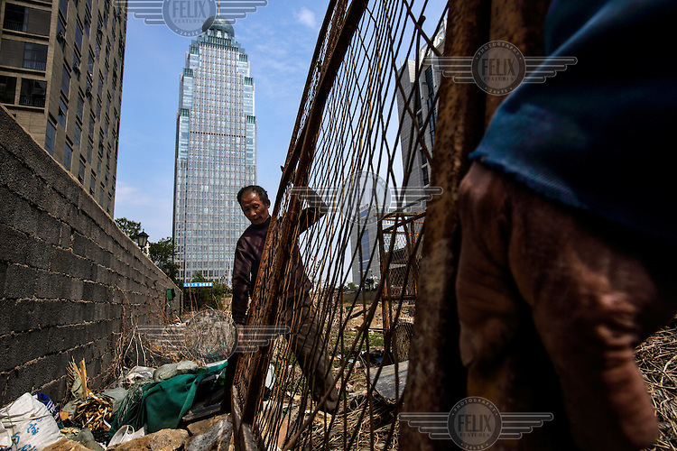 Former farmers build a new high-rise apartment building on a plot that was farmland just a few years ago. The local government is razing down this village on the outskirts of the city and turning farmland into an urban development zone. The Chinese government plans to move 250 million rural residents into urban areas over the coming dozen years though it is unclear whether people want to move and where the money for this project will come from. Further urbanisation is meant to drive up consumption to counterbalance an export orientated economy and end subsistence farming but the drive to get people off the land is causing tens of thousands of protests each year. /Felix Features