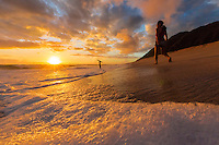Beachgoers enjoy the beautiful sunset at Yokohama Bay on the West Coast of O'ahu.