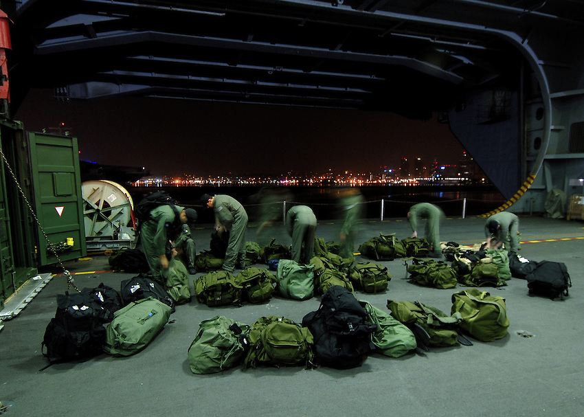 071021-N-7981E-009 Naval Air Station North Island (October 22, 2007)- Members of Helicopter Visit Board Search Seizure (HVBSS) Team 1 ready their gear for a non-compliant boarding exercise during the early morning hours aboard the Nimitz-class aircraft carrier USS Abraham Lincoln (CVN 72). HVBSS-1 is the first dedicated HVBSS team to reach operational status and they are currently training aboard Lincoln as part of the ship's scheduled work-up. U.S. Navy photo by Mass Communication Specialist 3rd Class James R. Evans (RELEASED)