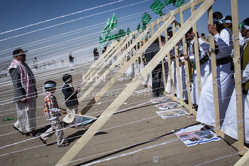 """Check point at the entrance of the Shia Houthi  celebration of the Prophet Mohammed's anniversary in the outskirts of Sana'a, where every individual has to step on the United States and Israel flags in order to get inside the venue. Tens of thousands gathered at the event. The Houthi slogan written on their headbands reads: """"Death to America, death to Israel, damn the Jews and victory to Islam""""."""
