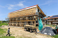 GERMANY, eco village Siebenlinden, construction site of building with straw bale and clay, behind straw bale house with sun collectors on the roof / DEUTSCHLAND, Oekosiedlung Siebenlinden in der Altmark, Baustelle eines neuen Wohnhaus aus einer Holzkonstruktion mit Strohballen , Hintergrund fertiges Strohballenhaus mit Lehm verputzter Wand und Solarkollektoren auf dem Dach