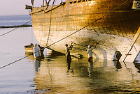 Kuwait October 1966.  Cleaning and Caulking a Dhow's Hull, Late Afternoon on the Sief Waterfront. AN ADDITIONAL 100 HISTORIC IMAGES OF KUWAIT MADE BETWEEN 1966-1972 ARE AVAILABLE.  LET US KNOW WHAT YOU NEED.