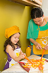 5 year old girl in kitchen with mother learning how to peel vegetable carrots