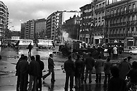Carrefour boulevard Lazare-Carnot et allées François-Verdier, devant le Monuments aux Combattants. 6 février 1978. Scène de manifestation : au 1er plan groupe de manifestants ; au 2nd plan pompiers en train d'éteindre un camion en feu, fumée, fourgons de police ; en arrière-plan perspective du boulevard Lazare-Carnot, plan d'ensemble façades. Cliché pris lors d'une manifestation organisée par une trentaine de transporteurs et artisans locaux pour protester contre le chantier de l'autoroute A61 donné à une grosse société du centre de la France. Manifestation patronée par la Confédération Intersyndicale de Défense et d'Union Nationale des Travailleurs Indépendants (CIDUNATI).