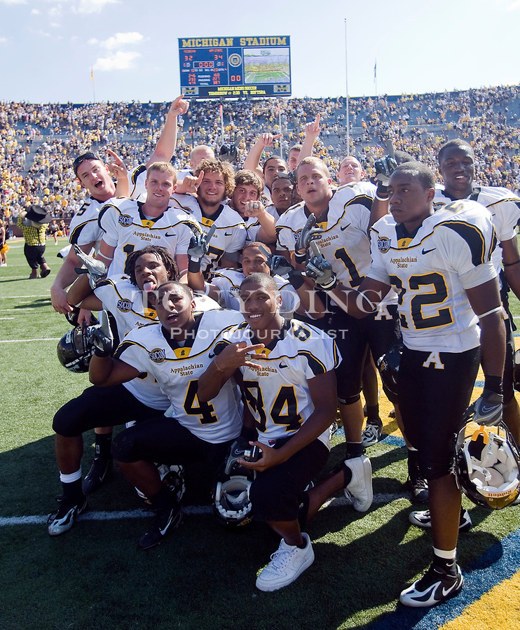 1 September 2007: Appalachian State players celebrate and pose for pictures at center field within Michigan Stadium after upsetting the no. 5 ranked Michigan Wolverines 34-32, in a 2007 college football season opener game, in Ann Arbor, MI.