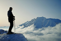 A lone skier overlooks a placid Alta Canyon from above the clouds from the top of Alf's High Rustler. Connotations - Conquering the peak, reaching the summit, reaching your goal. Utah, Alta Ski Resort.