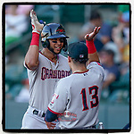 Pedro Gonzalez (4) of the Hickory Crawdads is greeted at the dugout steps after hitting a second-inning home run in a game against the Greenville Drive on Wednesday, June 16, 2021, at Fluor Field at the West End in Greenville, South Carolina. (Tom Priddy/Four Seam Images)