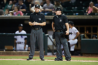Umpires Joe Belangia (left) and Dylan Bradley (right) between innings of the High-A East game between the Greensboro Grasshoppers and the Winston-Salem Dash at Truist Stadium on August 13, 2021 in Winston-Salem, North Carolina. (Brian Westerholt/Four Seam Images)