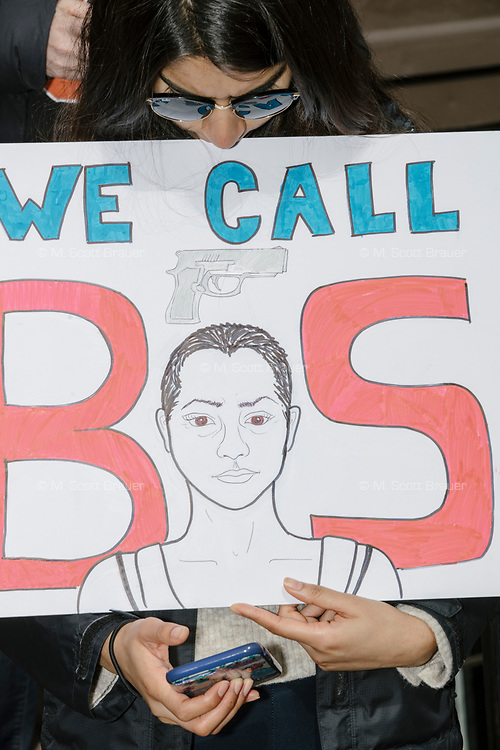 """A woman checks her phone while holding a sign reading """"We call BS"""" with a drawn image of Parkland shooting survivor Emma Gonzalez as people take part in the March For Our Lives protest, walking from Roxbury Crossing to Boston Common, in Boston, Massachusetts, USA, on Sat., March 24, 2018, in response to recent school gun violence."""