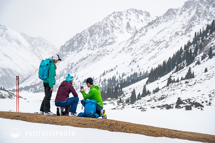 A group of skiers using the map on a phone while ski touring in Kyrgyzstan
