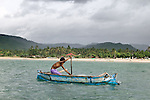 A young fisherman paddles his boat across the bay in Kuta, Lombok, Indonesia.