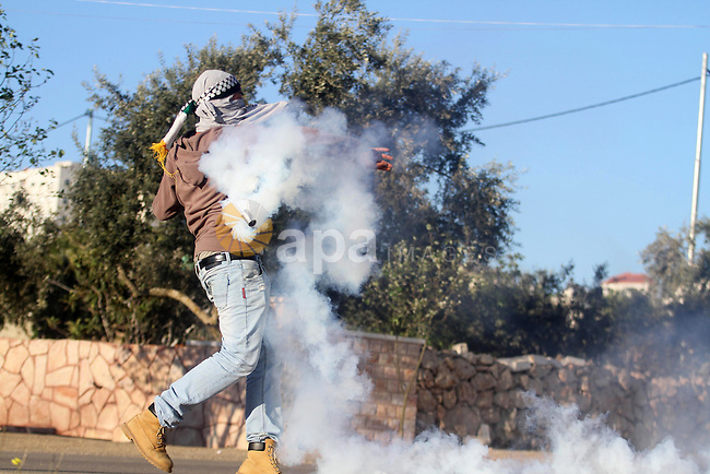 A Palestinian protester throws back a tear gas canister fired by Israeli security forces during clashes in the West Bank village of Silwad, north of Ramallah, on March 21, 2014 following a protest of Palestinians against the expansion of the nearby Israeli settlement of Ofra. Photo by Issam Rimawi