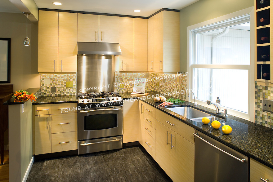 A contemporary Seattle kitchen remodel showcases marmoleum flooring, granite counters, recycled glass tiles in the backsplash, and bamboo upper and base cabinets in this eco-friendly design of a small but efficient space.
