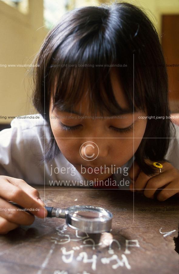 Indonesia Java Jakarta, girl with lens at school, Sequip project, promotion of science classes at schools in Jakarta / Indonesien Java Jakarta, Maedchen mit Lupe im naturwissenschaftlichen Unterricht , Sequip Projekt unterstuetzt durch GTZ deutsche Entwicklungshilfe