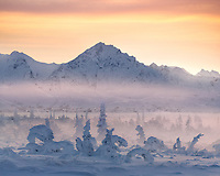 A snowy valley in Alaska's Chugach range is engulfed in fog and mist as the sun sets behind the mountains.