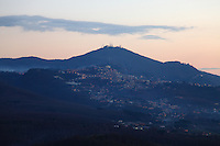 Tuscolo (near Monte Compatri): The view from the archeological park in the late afternoon, onto the facing small town of Molara, with some lights already turned on, the typical hill on the background with its antennas on the top, and some clouds.