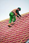 's GRAVENZANDE - Bouwvakker loopt op de daklatten van een steil dak bij een eengezinswoning van een nieuwbouwproject, en probeert zijn evenwicht te bewaren en niet te vallen. COPYRIGHT TON BORSBOOM