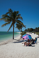 Sunbathers and Colorful Umbrellas at Sombrero Beach, Vaca Key, Marathon, Florida, FL, America, USA.