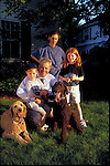 portrait of smiling family with pet dogs